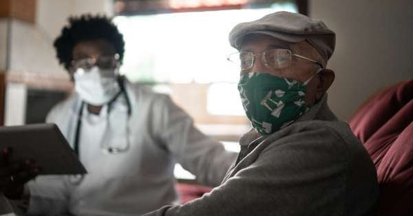 Portrait of senior patient and his doctor at home
