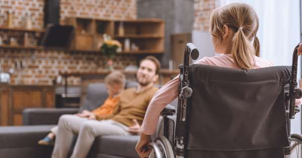 back view of disabled child sitting in wheelchair and looking at father and brother sitting on sofa at home