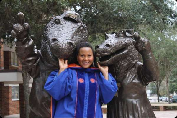 latoya allen stands with gator statues in her graduation robe